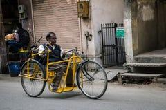 JAIPUR, ÍNDIA - 11 DE JANEIRO DE 2018: Uma pessoa deficiente que monta a com cadeira de rodas Tradicional, indiano, cadeira de ro Imagens de Stock