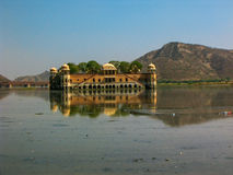 Jaipur floating palace on the lake, India. Reflection of palace. Calm water. Mountain in the background Royalty Free Stock Photo