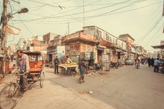 Street life with local food vendors, vehicles and poor houses of historical indian city Stock Photos