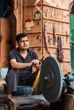 JAIPUR, INDIA - JANUARY 10, 2018: Man grinding on abrasive cutting and knife-sharpening stones. royalty free stock photography