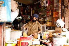 Jaipur, India - Jule 29: grocery store, man in a turban pours grain into a sack on Jule 29, 2011, Jaipur, India. Jaipur, India - Jule 29, 2011: grocery store stock photography