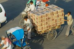 Rickshaw transports boxes with electronics by the street in Jaipur, India. stock photo