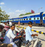People waiting at a railroad crossing in India Stock Photo