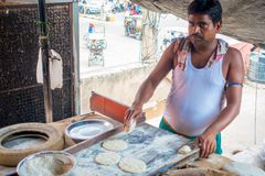 Jaipur, India - September 20, 2017: Unidentified man cooking Indian food over a wooden table with some material next to Royalty Free Stock Photos