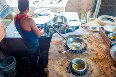 Jaipur, India - September 20, 2017: Unidentified man cooking Indian food over a wooden table with some material next to Stock Photo