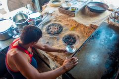 Jaipur, India - September 20, 2017: Unidentified man cooking Indian food over a wooden table with some material next to Stock Images
