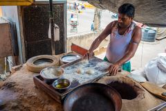 Jaipur, India - September 20, 2017: Unidentified man kneading the mass of an Indian food over a wooden table with some Royalty Free Stock Image
