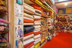 JAIPUR, INDIA - 19 SETTEMBRE 2017: Vista dell'interno del deposito del tessuto, con un bello mercato variopinto del tessuto indiv Fotografia Stock Libera da Diritti