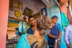 Jaipur India, Wrzesień, - 20, 2017: Fryzjer męski goli mężczyzna używa otwartego żyletki ostrze na ghats w Jaipur Zdjęcie Stock