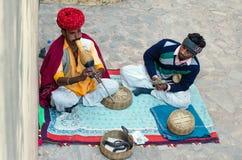 Jaipur, Indien - 29. Dezember 2014: Schlangenbeschwörer spielt die Flöte für die Kobra in Amber Fort Lizenzfreie Stockfotografie