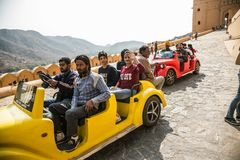 JAIPUR INDIEN - JANUARI 12, 2018: Folket rider en turist- elbil Amer Fort gul fort Royaltyfria Bilder