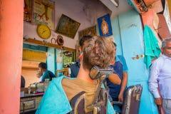 Jaipur Indien - September 20, 2017: Barberare som rakar en man som använder en öppen rakblad på ghatsna i Jaipur Royaltyfri Fotografi