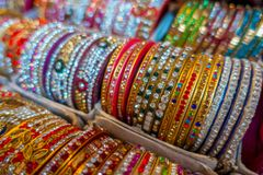 Jaipur Indien - September 20, 2017: Färgglade indiska handledarmband som staplas i högar på skärm på en shoppa Royaltyfri Bild