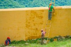 Jaipur Indien - September 19, 2017: Oidentifierade harworkers som målar en vägg med guling, en man i en trästege Arkivbilder