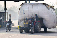 Jaipur, la India - 30 de diciembre de 2014: Hombre indio que conduce el camión pesadamente sobrecargado en Jaipur Foto de archivo libre de regalías