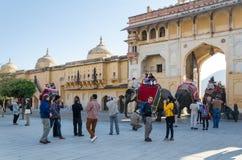 Jaipur, la India - 29 de diciembre de 2014: Los turistas disfrutan de paseo del elefante en Amber Fort Imagen de archivo libre de regalías