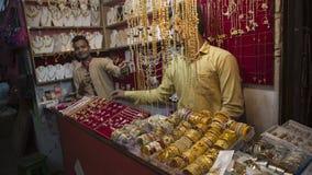 JAIPUR, LA INDIA, DICIEMBRE DE 2016: hombre que vende la joyería oriental del oro en el th Imágenes de archivo libres de regalías