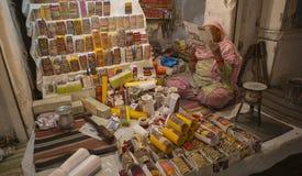JAIPUR, LA INDIA, DICIEMBRE DE 2016: Mujer que vende la joyería oriental del oro encendido Fotografía de archivo libre de regalías