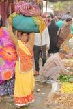 JAIPUR, RAJASTHAN INDIA, GRUDZIEŃ, - 06, 2017: Kolorowy warzywo rynek blisko miasto pałac z kobietą niesie ładunek na jej h Fotografia Stock