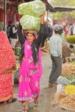 JAIPUR, RAJASTHAN INDIA, GRUDZIEŃ, - 06, 2017: Kolorowy warzywo rynek blisko miasto pałac z kobietą niesie ładunek na jej h Zdjęcie Stock