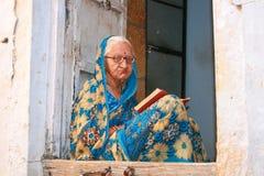 16.10.2012 - Jaisalmer。拉贾斯坦,印度。读书的年长妇女在他的门阶。 免版税库存照片