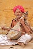 JAISALMER,拉贾斯坦,印度- 2017年12月20日:一位音乐家的画象有播放一传统inst的一条精密和五颜六色的头巾的 免版税库存照片