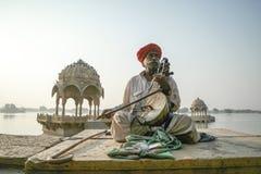 Jaisalmer Old Folk Musician. Jaisalmer, India- November 24, 2015:Unidentified nomads plays kamaycha in the Ghadisar Lake in Jaisalmer, India. Kamatcha is an Royalty Free Stock Photos