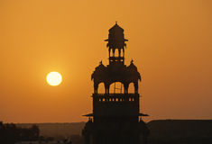 Jaisalmer sunset. Back lighting view at sunset of a maharajah palace tower in Jaisalmer. sky is golden by sand coming from close Thar desert. Rajasthan, India Stock Images