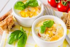 Jajeczna kokota w białym ramekin z pomidorem i basilem fotografia stock