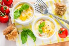 Jajeczna kokota w białym ramekin z pomidorem i basilem obrazy royalty free