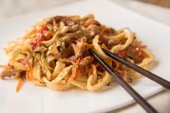Jajeczni udon kluski z wieprzowiną, warzywami i sezamowymi ziarnami na białym talerzu, Ñ  hinese chopsticks Fotografia Stock