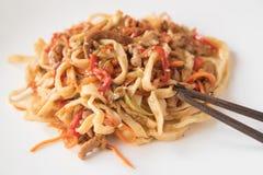 Jajeczni udon kluski z wieprzowiną, warzywami i sezamowymi ziarnami na białym talerzu, Zdjęcia Royalty Free