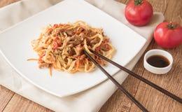 Jajeczni udon kluski z wieprzowiną, warzywami i sezamowymi ziarnami na białym talerzu, drewniany stół, Ñ  hinese chopsticks Zdjęcia Royalty Free