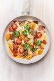 Jajeczny omelette w białym frypan z pomidorami, chlebem, serem i kiełbasą na białym drewnianym tle, odgórny widok Zdjęcie Royalty Free