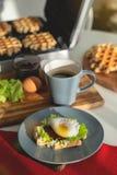 Jajka Benedykt z chlebem i pomidorem na talerzu z becon rankiem ściskają obrazy stock