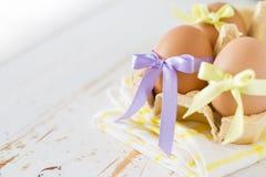 Jajka dekorowali z faborkiem na białym drewnianym tle Zdjęcia Royalty Free