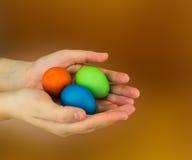 Jajka kłamają w palmach ręki czerwieni zieleni błękit na brown zamazanym tle Zdjęcie Royalty Free