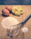 Jajka, mąka i inni surowi materiały na drewnianej desce, Obraz Royalty Free