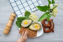 Jajka piec w avocado na talerzu z z rozciągania dziecka ` s ręką zdjęcie royalty free