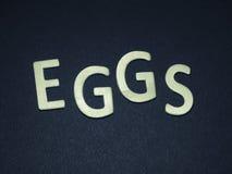 Jajka pisać z kolorowymi drewnianymi listami na błękitnym tle Zdjęcie Stock