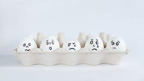 Jajka z śmiesznymi twarzami w pakunku na białym tle Wielkanocna pojęcie fotografia Twarze na jajkach obrazy royalty free
