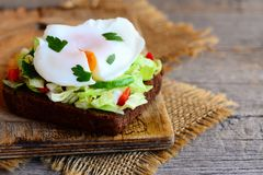 Jajko kłusująca kanapka Jajko kłusował na żyto chleba plasterku z świeżego warzywa sałatką Zdrowa kanapki fotografia Drewniany tł Fotografia Royalty Free