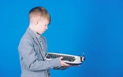 Jak robi retro pisa? na maszynie maszyny pracie M?drze dziecko u?ywa retro technologi? ?liczna ch?opiec z maszyn? do pisania Ma?y zdjęcia stock