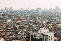 Jakarta Cityscape with high rise, skyscrapers and red tile hip roof local buildings with fog in the morning royalty free stock photo