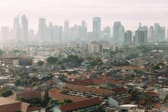Free Jakarta Cityscape With High Rise, Skyscrapers And Red Tile Hip Roof Local Buildings With Fog In The Morning Stock Image - 136192511
