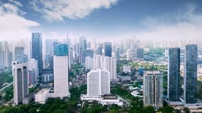 Jakarta downtown cityscape with skyscrapers and apartment buildings under blue sky. JAKARTA - Indonesia. March 12, 2018: Jakarta downtown cityscape with royalty free stock photos