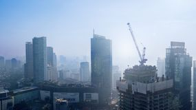 Jakarta downtown in the misty morning. JAKARTA - Indonesia. May 21, 2018: Aerial view of Jakarta downtown with high buildings in the misty morning Royalty Free Stock Image