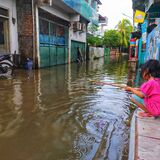 Jakarta flood kid with the stick toys to fill boring situation