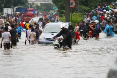 Jakarta Flood. People, motorcycles and cars crossing the flood in Jakarta royalty free stock images
