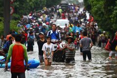Jakarta Flood. People, motorcycles and cars crossing the flood in Jakarta Stock Image
